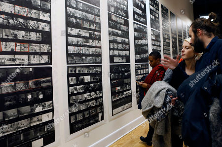"Spectators look at a wall of enlarged contact sheets of photographs for the book ""The Americans, "" by Robert Frank at the opening of an exhibition featuring his work, ""Robert Frank: Books and Films, 1947-2016,"" at New York University's Tisch School of the Arts, in New York. The exhibition also features correspondence and shots of such famous friends as Allen Ginsberg"