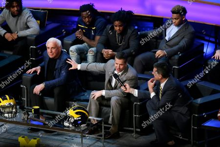 Jim Harbaugh, Ric Flair, John Harbaugh Baltimore Ravens head coach John Harbaugh, center, talks with brother Jim Harbaugh, right, as he tells a story about wrestler Ric Flair, left, as new recruits listen in during the Signing With the Stars spectacle, in Ann Arbor, Mich. College football's recruiting circus has found its ringmaster in Michigan's coach. Harbaugh was the real star of the Wolverines show that former coach Lou Holtz predicted will be copied in years to come by other schools