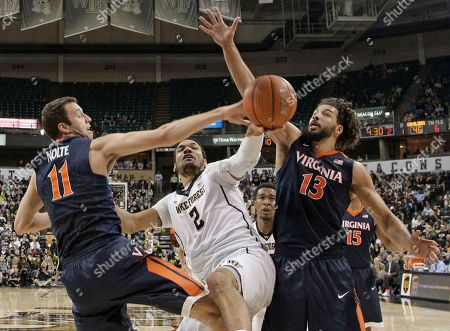 Devin Thomas, Anthony Gill, Evan Nolte Wake Forest's Devin Thomas (2) has his shot blocked as he drives between Virginia's Evan Nolte (11) and Anthony Gill (13) in the second half of an NCAA college basketball game in Winston-Salem, N.C., . Virginia won 72-71