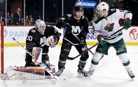 Jean-Francois Berube, Thomas Hickey, Jarret Stoll New York Islanders goalie Jean-Francois Berube (30) makes a save as Islanders defenseman Thomas Hickey (14) defends Minnesota Wild center Jarret Stoll (19) during the first period of an NHL hockey game in New York