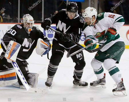 Jean-Francois Berube, Thomas Hickey, Jarret Stoll New York Islanders goalie Jean-Francois Berube (30) makes a save asslanders defenseman Thomas Hickey (14) defends Minnesota Wild center Jarret Stoll (19) during the first period of an NHL hockey game in New York