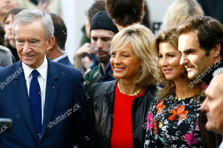Swiss tennis player Roger Federer, right, his wife Mirka, second right, French luxury group Chairman and CEO Bernard Arnault, left, his wife Helene Mercier smile during Louis Vuitton's Spring-Summer 2017 ready-to-wear fashion collection presented in Paris