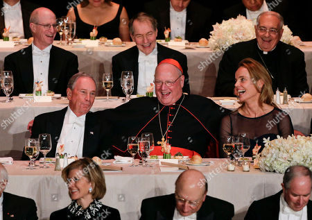 Cardinal Timothy Dolan, center, reacts with former New York Mayor Michael Bloomberg, left, and Maureen Sherry Klinsky, right, during opening remarks at the Alfred E. Smith Memorial Foundation dinner, in New York