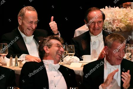 Senator Charles Schumer, D-NY, upper left, reacts to comments while sitting with Mortimer Zuckerman, publisher of the New York Daily News, during the Alfred E. Smith Memorial Foundation dinner, in New York