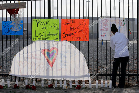 Melissa Smith writes a note at a makeshift memorial, in San Bernardino, Calif. A husband and wife on Wednesday, dressed for battle and carrying assault rifles and handguns, opened fire on a holiday banquet for his co-workers, killing multiple people and seriously wounding others in a precision assault, authorities said. Hours later, the couple died in a shootout with police