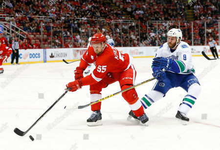Detroit Red Wings defenseman Niklas Kronwall (55) keeps the puck from Vancouver Canucks right wing Brandon Prust (9) in the second period of an NHL hockey game in Detroit