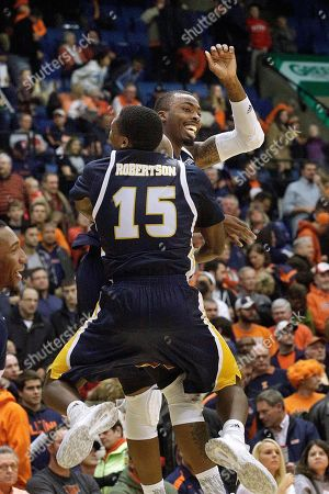 Chattanooga guard Eric Robertson (15) jumps and hugs forward Justin Tuoyo, back, at the end of an NCAA college basketball game against Illinois at the Prairie Capital Convention Center, in Springfield, Ill. Chattanooga defeated Illinois 81-77