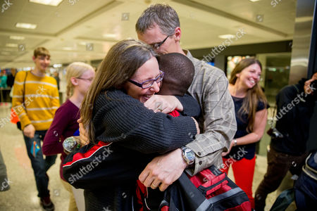 Stock Image of Jennifer Sands, Issaac Sands Jennifer and Eric Sands of Illinois hug their adopted son Issaac, 12, as he arrives from the Congo at Dulles International Airport, Dulles, Va. After a wait of more than two years, American families celebrated on U.S. territory after 14 children from the Congo were granted long-stalled exit permits while more then 400 families are still waiting to be approved by the Congolese government