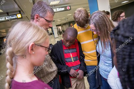 Stock Image of Jennifer Sands, Eric Sands, Issaac Sands, Mathew Sands, Grace Sands Jennifer and Eric Sands of Illinois, right, accompanied by their children Grace, 12, left, and Mathew 16, second from right, pray in a circle with their adopted son Issaac, 12, center, after he arrives from the Congo at Dulles International Airport, in Dulles, Va. After a wait of more than two years, American families celebrated on U.S. territory after 14 children from the Congo were granted long-stalled exit permits while more then 400 families are still waiting to be approved by the Congolese government