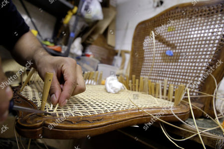 In this, photo, Diego Martin hand canes a chair at the Veterans Caning & Repair shop in New York. In a dusty, cluttered shop that seems oddly out of place in modern New York, a group of artisans is among the last still practicing a dying trade: chair caning. The painstaking art of weaving furniture details in a honeycomb pattern is still in demand, mostly for repair work, but the shop that's been around since 1899 is under threat from a new wave of high-rise development on Manhattan's west side