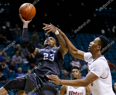 Massachusetts forward Malik Hines, right, fouls Creighton guard James Milliken during the second half of an NCAA college basketball game, in Las Vegas