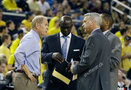 Stock Image of John Beilein, Bacari Alexander, Jeff Meyer From left, Michigan head coach John Beilein, assistant coaches Bacari Alexander, Jeff Meyer and LaVall Jordan huddle on the court during a break in the second half of an NCAA college basketball game against Delaware State, in Ann Arbor, Mich