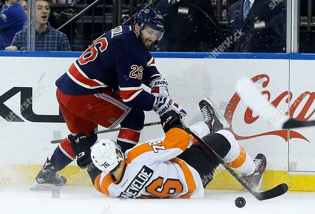 Philadelphia Flyers center Chris VandeVelde (76) loses his footing as he fights for control of the puck against New York Rangers center Jarret Stoll (26) during the second period of an NHL hockey game, in New York