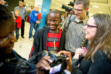 Stock Image of Jennifer Sands, Eric Sands, Issaac Sands, Joy Sands Jennifer and Eric Sands of Illinois, right, accompanied by their adopted daughter Joy, 12, left, smile as their adopted son Issaac, 12, center arrives from Congo at Dulles International Airport, in Dulles, Va. The number of foreign children adopted by U.S. parents dropped by 12 percent last year to the lowest level since 1981, according to new State Department figures. Even with the decline, Ethiopia was No. 2 on the list, followed by South Korea, Ukraine, Uganda, Bulgaria, Latvia and Congo