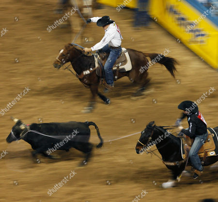 With a slow shutter speed, Trevor Brazile, bottom, and Patrick Smith compete in the team roping event for a first place during the seventh go-round of the National Finals Rodeo, in Las Vegas