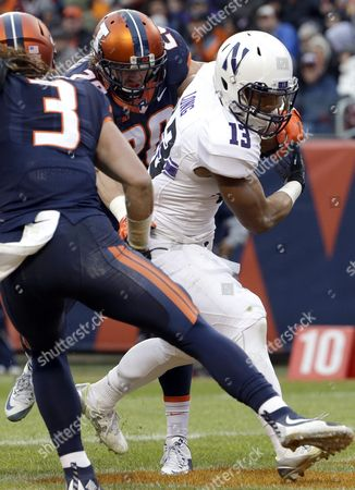 Stock Picture of Warren Long, Taylor Barton, Clayton Fejedelem Northwestern running back Warren Long (13) scores a touchdown past Illinois strong safety Taylor Barton, left, and free safety Clayton Fejedelem during the first half of an NCAA college football game, in Chicago