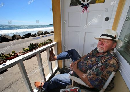 """Michael Gross Artist Michael Gross, sits on the porch of his ocean front bungalow where he paints and produces other art in his studio in Oceanside, Calif. Gross, an artist who created two of the most distinctive pop culture images of the 20th century, died . He was 70. Gross first gained wide attention in 1973 for the National Lampoon cover of a dog with a gun to its head and the words, """"If You Don't Buy This Magazine, We'll Kill This Dog."""" A decade later, he created the enduring symbol of a confused looking ghost in the middle of a slashed red circle for the film """"Ghostbusters"""