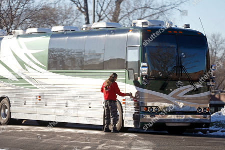 An unidentified man enters the tour bus of singer Scott Weiland, the former frontman for the Stone Temple Pilots and Velvet Revolver, in Bloomington, Minn. A statement on his Facebook page said Weiland, 48, who was dogged by substance abuse problems throughout his career, died in his sleep on the bus Thursday night while parked at a Bloomington hotel