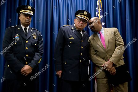 Philadelphia Police Commissioner Charles Ramsey, center, listens to Mayor Michael Nutter as Philadelphia Police Deputy Commissioner Richard Ross stand during a news conference, in Philadelphia. Justice Department officials are praising the Philadelphia Police Department for its progress in implementing reforms after a federal probe on deadly force. The report issued in May found the department's use of deadly force was motivated by fear and affected mostly black citizens