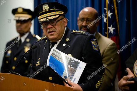 Philadelphia Police Commissioner Charles Ramsey, center, refers to the Justice Department's six-month assessment report in his hand as Mayor Michael Nutter, right, and Deputy Commissioner Richard Ross, left, listen during a news conference, in Philadelphia. Justice Department officials are praising the Philadelphia Police Department for its progress in implementing reforms after a federal probe on deadly force. The report issued in May found the department's use of deadly force was motivated by fear and affected mostly black citizens