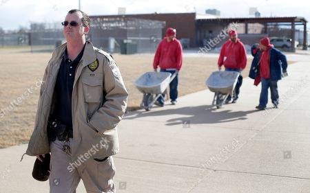 Corrections officer Jason Smith escorts an inmate work crew at the Ellsworth Correctional Facility in Ellsworth, Kan. Low wages among Kansas corrections officers are causing many to leave the field, leaving about 9 percent of the positions in the state's prisons unfilled