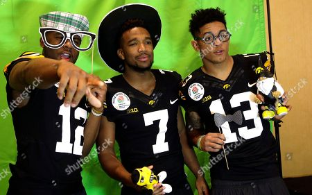 Iowa football teammates defensive back Anthony Gair, left joins Sean Draper, center and Greg Mabin at a photo booth during Media Day at The L.A. Downtown Hotel in downtown Los Angeles on . Iowa is scheduled to play Stanford in the Rose Bowl NCAA college football game on New Year's Day