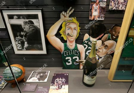 A depiction of former Boston Celtics basketball player Larry Bird, center, rests in a display case near a photograph of former Celtics coach Red Auerbach, left, in an exhibit in the Sports Museum at the TD Garden, in Boston. Curators have teamed up with professional archivists to preserve the estimated $7 million collection, much of which is kept in off-site storage that was threatened by last winter's historic snows