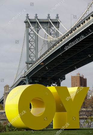 """The Manhattan Bridge towers over a bright yellow monumental sculpture by artist Deborah Kass in Brooklyn Bridge Park, in New York. When viewed from Manhattan, the sculpture reads the urban slang word """"Yo,"""" but when viewed from Brooklyn, it spells the popular Yiddish expression """"Oy."""" The aluminum sculpture was commissioned by Brooklyn developer Two Trees Management Company and will remain up until August 2016"""