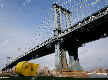 """A bright yellow monumental sculpture by artist Deborah Kass sits below the Manhattan Bridge in Brooklyn Bridge Park, in New York. When viewed from Manhattan, the sculpture reads the urban slang word """"Yo,"""" but when viewed from Brooklyn, it spells the popular Yiddish expression """"Oy."""" The aluminum sculpture was commissioned by Brooklyn developer Two Trees Management Company and will remain up until August 2016"""