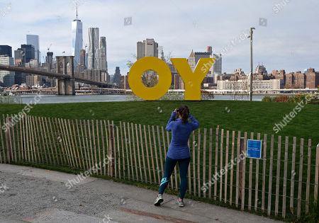 """A runner pauses to snap a cell phone photo of a bright yellow monumental sculpture by artist Deborah Kass in Brooklyn Bridge Park, in New York. When viewed from Manhattan, the sculpture reads the urban slang word """"Yo,"""" but when viewed from Brooklyn, it spells the popular Yiddish expression """"Oy."""" The aluminum sculpture was commissioned by Brooklyn developer Two Trees Management Company and will remain up until August 2016"""