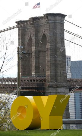 """Stock Image of One tower of the Brooklyn Bridge is visible above a bright yellow monumental sculpture by artist Deborah Kass in Brooklyn Bridge Park, in New York. When viewed from Manhattan, the sculpture reads """"Yo,"""" but when viewed from Brooklyn it spells the popular Yiddish expression """"Oy."""" The aluminum sculpture was commissioned by Brooklyn developer Two Trees Management Company and will remain up until August 2016"""