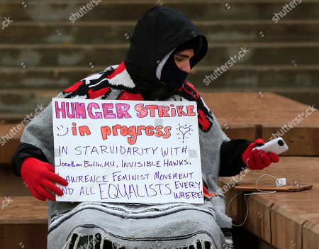 """Hunger striker John Cowan, a a 2014 University of Kansas graduate, checks his phone while protesting on the University of Kansas campus, in Lawrence, Kan. Protest leaders at the University of Kansas said Monday that they're pushing for changes that ensure problems faced by minority and other """"marginalized"""" students are addressed swiftly and effectively, rather than """"mimicking Mizzou"""" by seeking the ouster of administrators"""