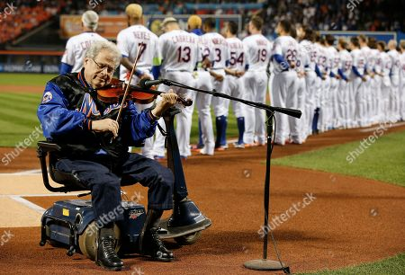 Musician Itzhak Perlman plays the national anthem before the start the National League wild-card baseball game between the New York Mets and the San Francisco Giants, in New York