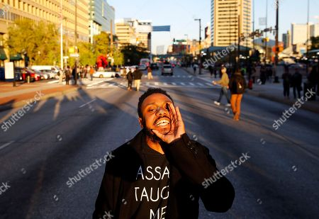 A protester chants in the middle of a street as the sun sets, in Baltimore, after the City Council confirmed Kevin Davis as the city's permanent police commissioner. The council's vote came five days after a committee voted in favor of hiring Davis and demonstrators held a sit-in to demand meetings with Davis and Baltimore Mayor Stephanie Rawlings-Blake