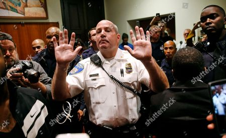 A member of the Baltimore City Police Department clears protestors out of City Hall after the City Council confirmed Kevin Davis as the city's permanent police commissioner, in Baltimore. The council's vote came five days after a committee voted in favor of hiring Davis and demonstrators held a sit-in to demand meetings with Davis and Baltimore Mayor Stephanie Rawlings-Blake