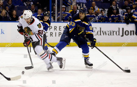 Stock Photo of Erik Gustafsson, Scott Gomez Chicago Blackhawks' Erik Gustafsson, of Sweden, controls the puck as St. Louis Blues' Scott Gomez (93) watches during the second period of an NHL preseason hockey game, in St. Louis