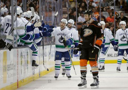 Clayton Stoner, Brandon Prust Vancouver Canucks' Brandon Prust, center, and teammates celebrate a goal by Adam Cracknell as Anaheim Ducks' Clayton Stoner, foreground, skates toward the bench during the second period of an NHL hockey game, in Anaheim, Calif
