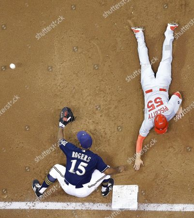 St. Louis Cardinals' Stephen Piscotty (55) slides safely back to first with Milwaukee Brewers' Jason Rogers covering on a pick off attempt during the third inning of a baseball game, in Milwaukee