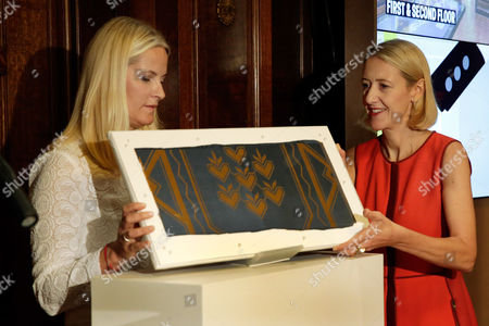Crown Princess Mette-Marit, Caroline Baumann Crown Princess Mette-Marit of Norway, left, and Cooper Hewitt Director Caroline Baumann, hold the gift of a Norwegian textile to Cooper Hewitt's wallcoverings collection, during ceremonies at the Cooper Hewitt, Smithsonian Design Museum,in New York. The original wallpaper is from the United Nations Security Chamber, donated to the UN in 1952