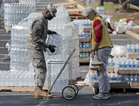 Army National Guard Spl. John Stephens, left, gives J.E. Briggs, right, bottled water in Columbia, S.C., . Water distribution remained a key problem Tuesday across much of the state. In Columbia, as many as 40,000 homes lacked drinking water, and the rest of the city's 375,000 customers were told to boil water before using it for drinking or cooking