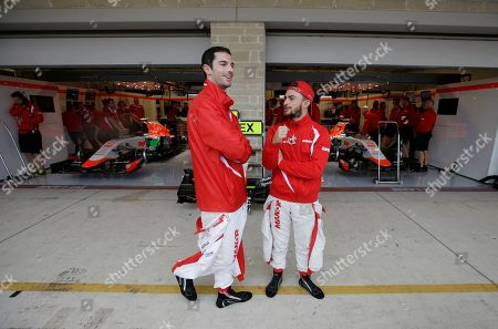 Manor driver Alexander Rossi, left, and Will Stevens, of Britain, stand outside of their garage during a rain delay before the start qualifying for the Formula One U.S. Grand Prix auto race at the Circuit of the Americas, in Austin, Texas
