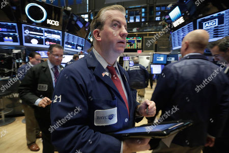 James Doherty Trader James Doherty, center, works on the floor of the New York Stock Exchange, . Stocks are edging lower Thursday morning, giving back some of the gains they made the day before
