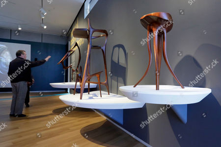 """Walnut Sculpture, Scribe's Stool, Stool Walnut Sculpture,"""" """"Scribe's Stool,"""" and """"Stool,"""" left to right, part of the Wendell Castle Remastered exhibit, are displayed at the Museum of Arts and Design, in New York. The museum show explores the recent work of Wendell Castle, 83, sometimes called the father (or grandfather) of the American art furniture movement for pieces that are both sculpture and furniture"""