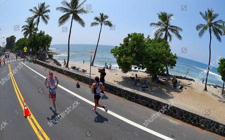 Jan Frodeno, Rachel Joyce Jan Frodeno, left, of Germany, runs by Rachel Joyce, of Great Britain, during the marathon portion of the Ironman World Championship Triathlon, in Kailua-Kona, Hawaii. Frodeno won the Men's portion of the event and Joyce took second in the Women's portion