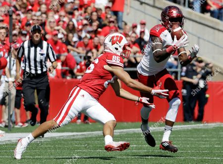 Miami of Ohio's Marshall Taylor intercepts a pass in front of Wisconsin's Alex Erickson (86) during the first half of an NCAA college football game, in Madison, Wis