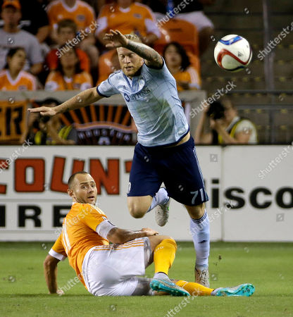 Brad Davis, Marcel de Jong Sporting Kansas City's Marcel de Jong (71) jumps over Houston Dynamo's Brad Davis (11) during the first half of a MLS soccer match, in Houston