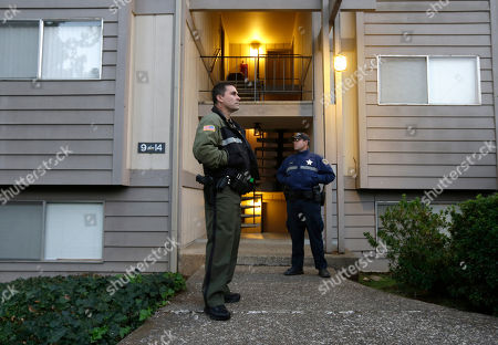 Douglas County Deputy Sheriff Greg Kennerly, left, and Oregon State Trooper Tom Willis stand guard outside the apartment building where alleged Umpqua Community College gunman Chris Harper Mercer lived with his mother in Roseburg, Ore. The deadly shooting last week has an eerie parallel with the massacre at Sandy Hook Elementary School that killed 20 pupils and six adult staff members in 2012. Like Adam Lanza, the gunman in the Connecticut massacre, Christopher Harper-Mercer was living a mostly solitary life with a mom who shared his fascination with firearms