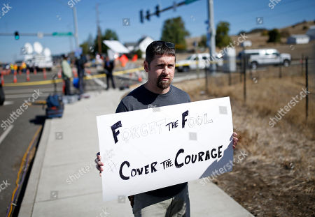 Mike Scott holds up a sign near the road that leads to Umpqua Community College, in Roseburg, Ore. Armed with multiple guns, Chris Harper Mercer, 26, walked in a classroom at the community college, Thursday, and opened fire, killing several and wounding several others