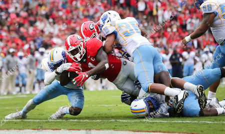 Stock Image of Sony Michel, Justin Morgan, Nicholas mcDonald Georgia running back Sony Michel (1) reaches for the goal line as Southern's Justin Morgan (9) and Nicholas McDonald (36) defend in the first half of an NCAA college football game, in Athens, Ga