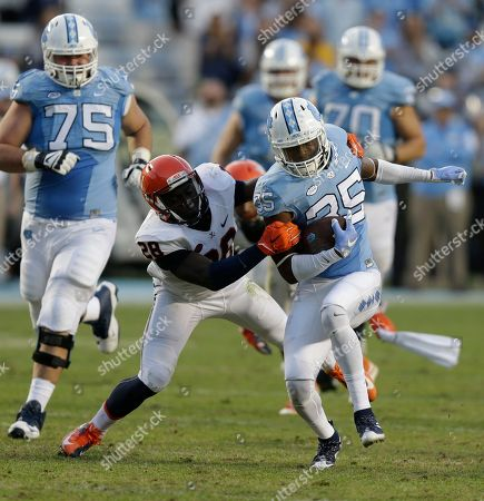Stock Image of Damien Washington, Wilfred Wahee North Carolina's Damien Washington (35) runs the ball as Virginia's Wilfred Wahee (28) looks to tackle during the second half of an NCAA college football game in Chapel Hill, N.C., . North Carolina won 26-13